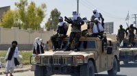 Para pejuang Taliban terlihat berdiri di atas barisan Humvee selama parade sepanjang jalan di Kandahar