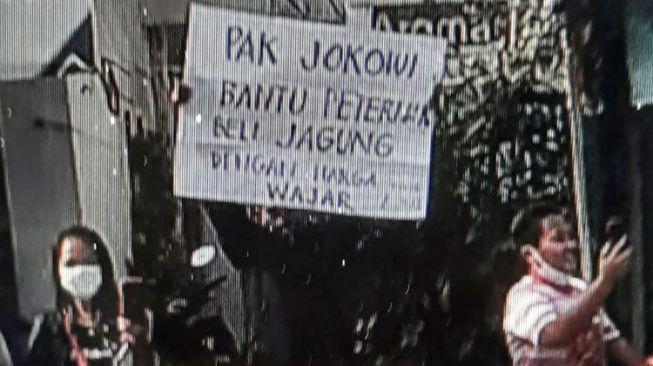 Tangkapan layar video seorang pria membentangkan poster saat kunjungan Presiden Jokowi ke Kota Blitar